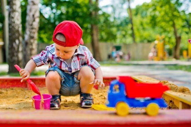 Dreng som leger i sandkasse med sandkasse legetøj